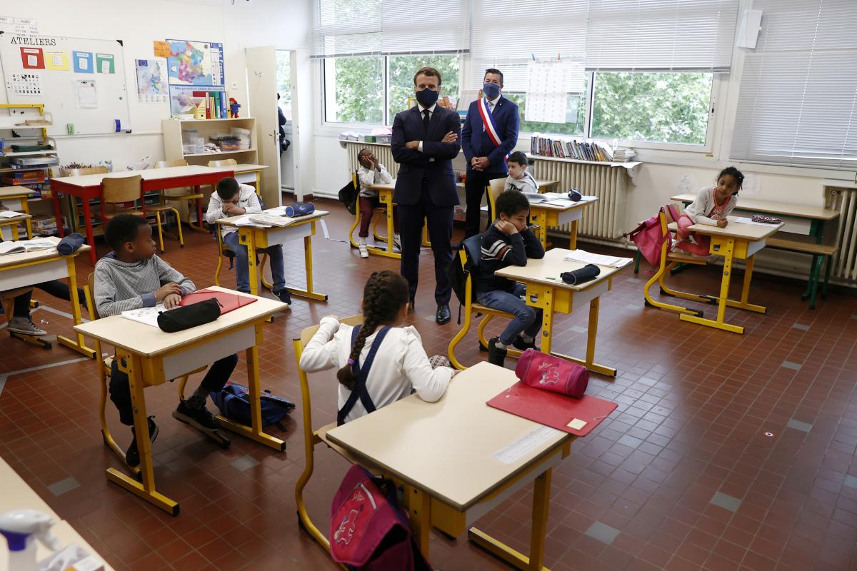 Macron habla con los hijos de personal sanitario, policías y otro personal indispensable. durante su visita a una escuela en Poissy.