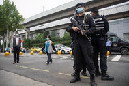 Policías vigilan la entrada de un instituto, en Wuhan.