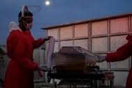 Sepultureros preparan el ataúd de un fallecido con sospechas de Covid-19, en un cementerio de Río de Janeiro.