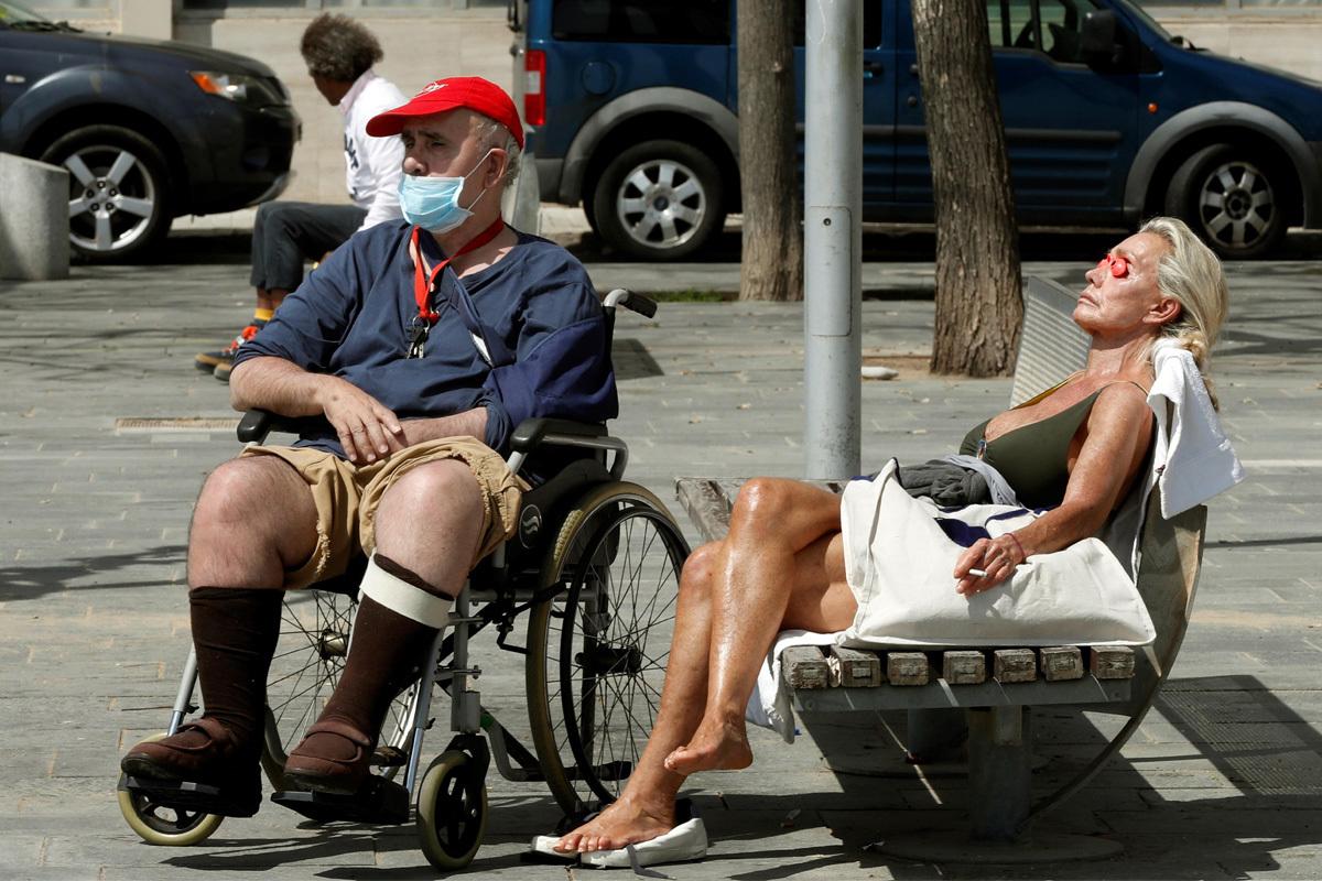 Dos personas toman el sol, este miércoles, en el paseo marítimo de Barcelona.