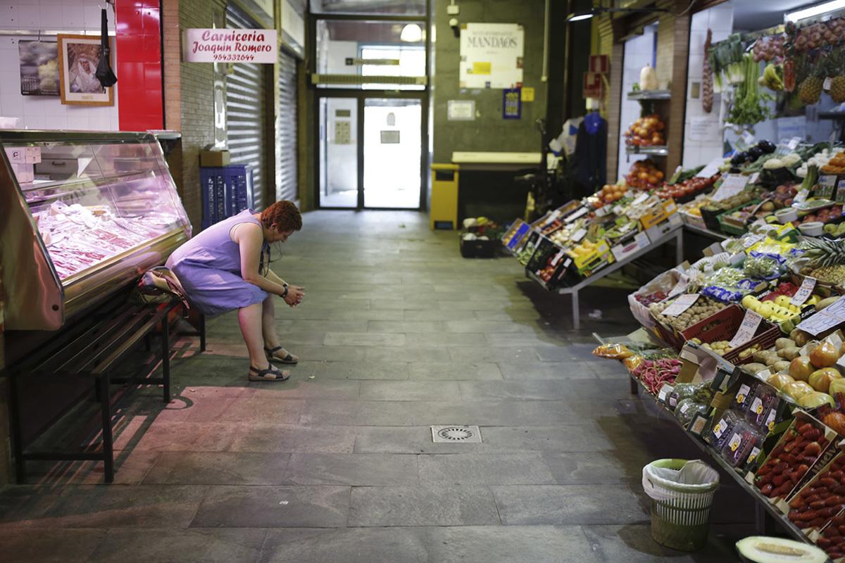 Una mujer sentada ante su puesto de verduras, este lunes, en un mercado de Sevilla.