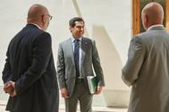El presidente de la Junta, Juanma Moreno, junto a dos diputados de Vox en los pasillos del Parlamento.