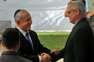 Netanyahu y Gantz se estrechan la mano durante una ceremonia.