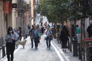 Vecinos pasean durante una de las franjas permitidas por una calle peatonal de Malasaña