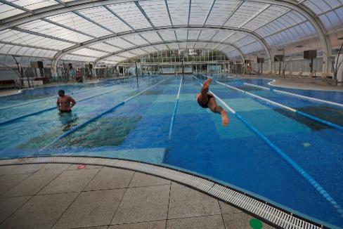 Dos bañistas nadan en una piscina cubierta en Barcelona.