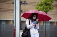 Una joven con mascarilla y guantes mira su móvil.