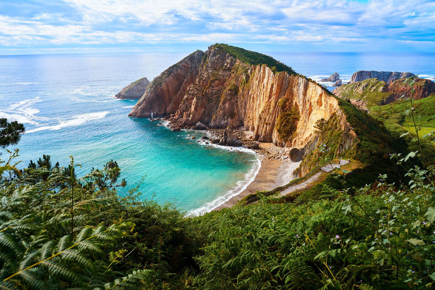 """Es una de las playas más bonitas del Principado y de toda España. Ubicada a 16 kilómetros de  <a href=""""https://www.elmundo.es/viajes/espana/2020/01/25/5e286f90fdddff36808b46cd.html"""" target=""""_blank"""">Cudillero</a> y con forma de concha, está rodeada de cantos rodados de 500 metros que ocultan un <strong>paraje virgen salpicado de acantilados.</strong> Estos la protegen de las embestidas del mar, que acaban convirtiéndose en un estremecedor arrullo. De ahí su nombre, aunque también la llaman<strong> El Gavieiru.</strong> Para acceder, hay que bajar unas escaleras escarpadas que acaban en la playa tras una caminata en medio de la naturaleza."""