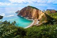 """Es una de las playas más bonitas del Principado y de toda España. Ubicada a 16 kilómetros de  <a href=""""https://www.elmundo.es/viajes/espana/2020/01/25/5e286f90fdddff36808b46cd.html"""" target=""""_blank"""">Cudillero</a> y con forma de concha, está rodeada de cantos rodados de 500 metros que ocultan un <strong>paraje virgen salpicado de acantilados.</strong> Estos la protegen de las embestidas del mar, que acaban convirtiéndose en un estremecedor arrullo. De ahí su nombre, aunque también la llaman<strong> El Gavieiru.</strong> Para acceder, hay que bajar unas escaleras escarpadas que acaban en la playa tras una caminata en plena naturaleza."""