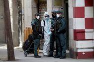Agente de la Guardia Civil hacen guarda a la puerta del domicilio del detenido.