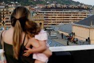 Una mujer con su hija observan el concierto de Izaro en la terraza del Victoria Eugenia de San Sebastián.