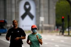 Dos personas hacen deporte este sábado junto a la Puerta de Alcalá de Madrid.