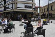 Clientes disfrutan del buen tiempo en una terraza del centro de Vitoria.