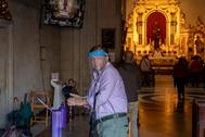 Un hombre con máscara se aplica gel desinfectante en el interior de la Basílica de Jesús del Gran Poder en Sevilla.
