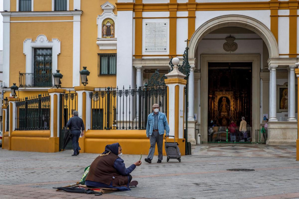 Una mujer pide limosna en la entrada de la iglesia de la Macarena, reabierta desde el lunes 11.