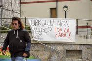 Una vecina de Zaldibar camina junto a un cartel crítico con la gestión del Gobierno de Urkullu.