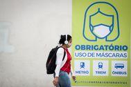 AME9526. SAO PAULO ( lt;HIT gt;BRASIL lt;/HIT gt;).- Una joven camina frente a un letrero que indica que el uso de la máscara es obligatorio en el transporte público este miércoles, en Sao Paulo ( lt;HIT gt;Brasil lt;/HIT gt;). Con más de 12.400 muertos por coronavirus, lt;HIT gt;Brasil lt;/HIT gt;, epicentro latinoamericano de la pandemia, encara el creciente avance de la enfermedad en medio de un pulso entre los gobernadores y el presidente Jair Bolsonaro, quien presiona por abrir hasta los gimnasios y peluquerías del país.