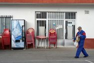 Un hombre camino frente a un bar cerrado en Solana de Rioalmar (Ávila)