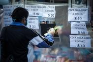 AME7451. BUENOS AIRES (ARGENTINA), 03/05/2020.- Un hombre realiza compras en un comercio protegido por plásticos este domingo, durante un nuevo día de cuarentena obligatoria por la pandemia de COVID-19, en Buenos Aires (Argentina). El país sigue bajo el aislamiento social obligatorio que comenzó el pasado 20 de marzo, y el pasado viernes el Gobierno de lt;HIT gt;Alberto lt;/HIT gt; lt;HIT gt;Fernández lt;/HIT gt; habilitó un nuevo permiso para el traslado excepcional de aquellas personas que estén cumpliendo la cuarentena en un domicilio distinto al de su residencia habitual en el país y deseen regresar a sus hogares en vehículos particulares.