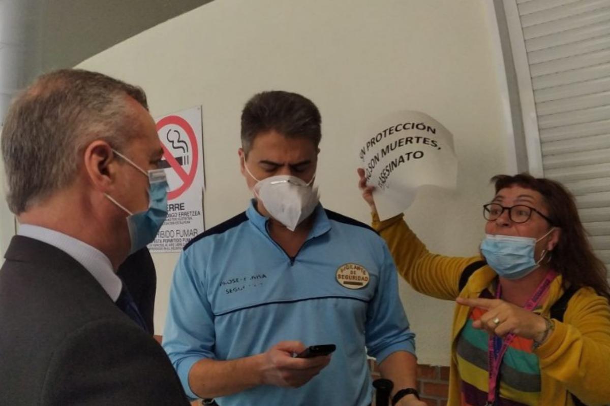 Ainhoa Gutiérrez con su cartel, enfrentándose a Urkullu (izquierda), este lunes en el Hospital de Cruces (Vizcaya).