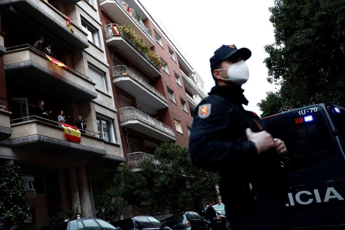 Efectivos de la Policía vigilan mientras vecinos del madrileño barrio de Salamanca se manifiestan en la calle y en sus balcones.