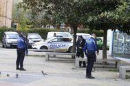 Dos agentes de la policía local de Madrid abordan a un hombre sentado en un parque.