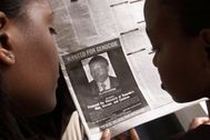 FILE PHOTO: READERS LOOK AT A PICTURE OF A RWANDAN WANTED FOR ALLEGED ROLE IN RWANDA'S 1994 GENOCIDE