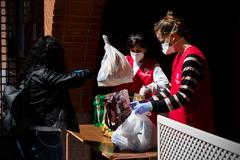 Voluntarias de Cáritas reparten comida en la parroquia de Santa Irene de Vallecas (Madrid).