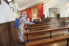 Un trabajador de una empresa privada desinfectan una capilla en Málaga.