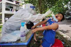 Un sanitario recoge muestras a un niño en Wuhan, China