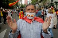 Un señor, con mascarillas de España, en las protestas en Madrid