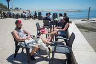 Unas personas toman el sol en una terraza junto al mar en Málaga.