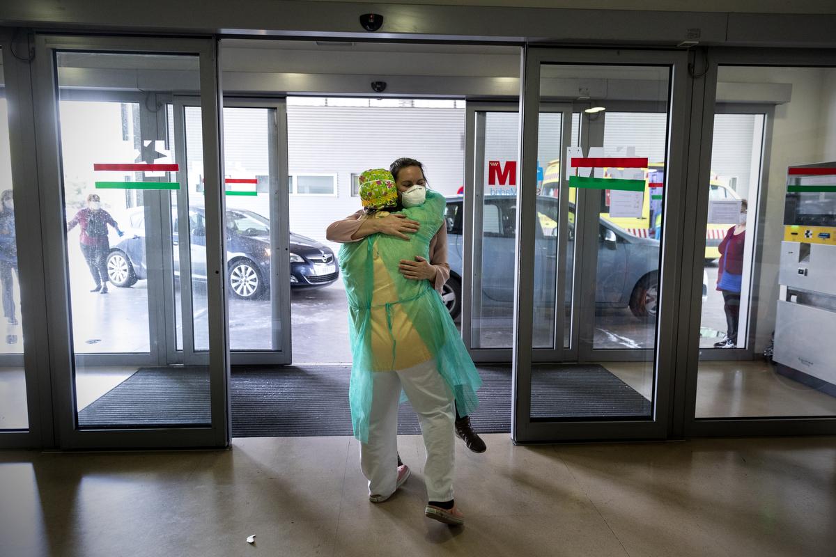 Alicia, la hija de Fernando, se abraza a una compañera del hospital antes llevar a su padre a casa.