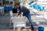 Un trabajador limpia las mesas de una cafetería, ayer, en el Grao de Castellón.