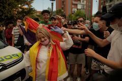 Radicales insultan a una mujer con la bandera de España.