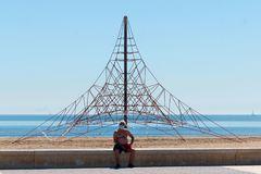 Un hombre con mascarilla descansa frente a la playa de la Malva-rosa de Valencia.