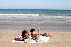 Dos bañistas con mascarillas en la playa de la Malvarrosa, en Valencia.
