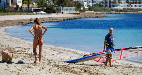 Varias personas disfrutando de una playa de Ibiza.