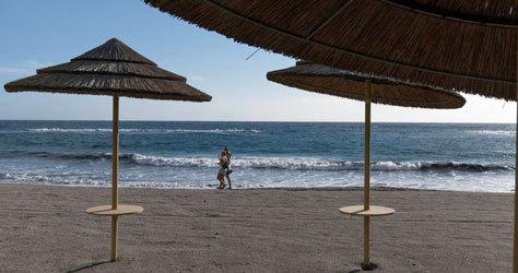 Paseantes una la playa de Fañabé, en Tenerife.