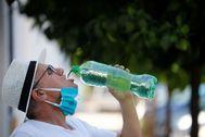 Un hombre se quita la mascarilla para beber agua en Córdoba.