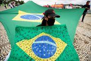 """AME1058. BRASILIA ( lt;HIT gt;BRASIL lt;/HIT gt;).- Una mujer sostiene una bandera de lt;HIT gt;Brasil lt;/HIT gt; con cruces negras pintadas por las víctimas de covid-19 en ese país, durante una protesta contra el presidente de lt;HIT gt;Brasil lt;/HIT gt;, Jair Bolsonaro, este miércoles, en el Palacio de Planalto en Brasilia ( lt;HIT gt;Brasil lt;/HIT gt;). Convocados por los miembros del comité popular """"Fuera Bolsonaro"""", decenas de personas participaron en la manifestación que rechaza las declaraciones y las acciones por parte de Bolsonaro durante el manejo de la crisis por coronavirus, que deja más de 17.000 muertes en el país sudamericano."""