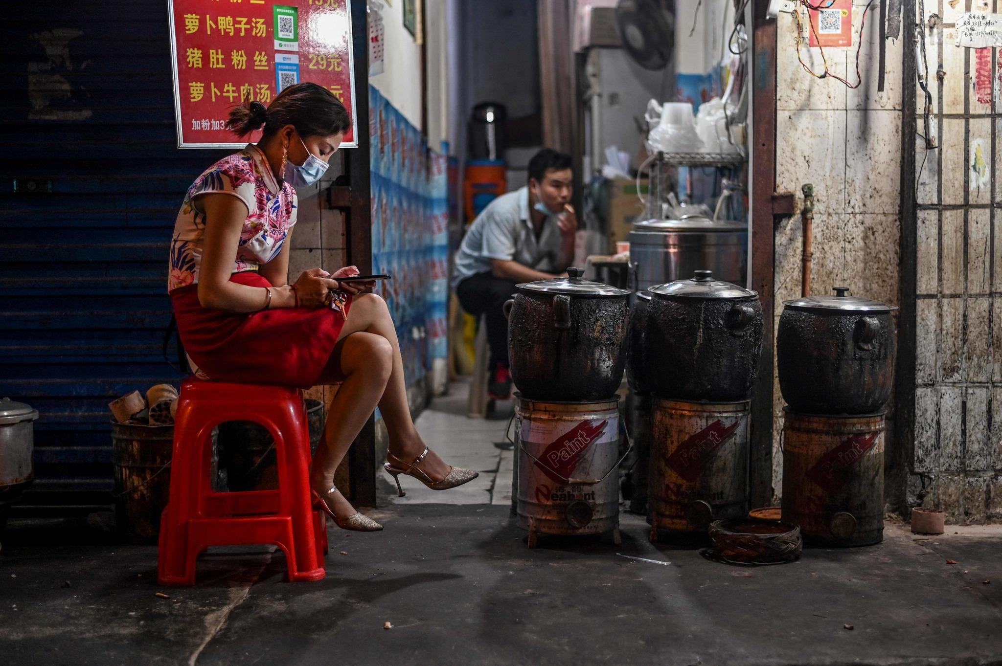 Una mujer protegida con mascarilla espera la llegada de clientes a su puesto de Wuhan.