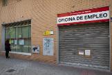 Una mujer mira el escaparate cerrado de una oficina pública de empleo.