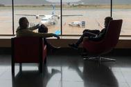 Pasajeros con mascarilla para el coronavirus aguardan el embarque de un vuelo a Palma de Mallorca.