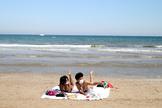 Dos jóvenes con mascarilla toman el sol en la playa de La Malvarrosa, una actividad prohibida en la Fase 1 de la desescalada.