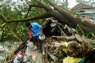 Un hombre recupera algunas pertenencias de su casa destrozada al paso del ciclón.