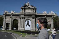 Un madrileño con mascarilla pasea frente a la Puerta de Alcalá.