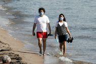 Dos jóvenes pasean por la playa con mascarilla.