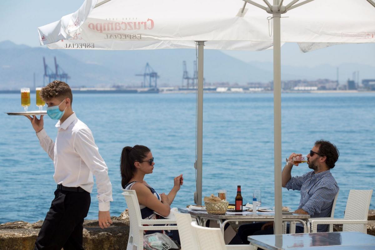 Una pareja come en una terraza de Málaga tras la reapertura de los restaurantes de la provincia.