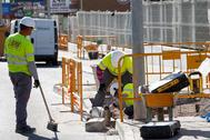 Tres obreros trabajan en la acera de una calle de Castellón.