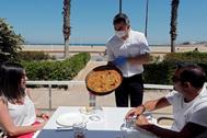 Un camarero sirve una paella en una terraza de la playa de la Malvarrosa de Valencia